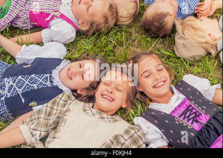 Germany, Saxony, group of children wearing traditional clothes lying on a meadow in circle - Stock Photo
