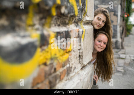 Two teenage girls look out behind the corner of the house. - Stock Photo