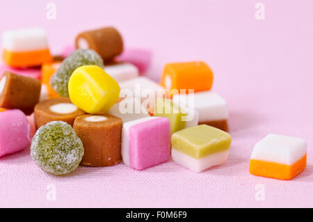 Close up of dolly mixture sweets on pink background - Stock Photo