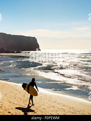 Surfer walking on the beach in the sunshine day. Portugal - Stock Photo