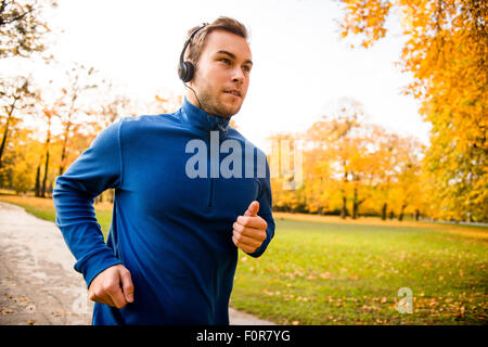Young man with headphones running in autumn nature and listening music - Stockfoto