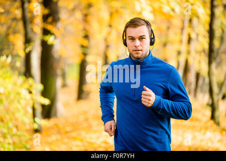 Young man with headphones jogging in autumn nature and listening music - Stockfoto