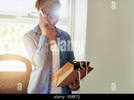 Young businesswoman chatting on the telephone as she discusses packaging for the products for sale in her new e - Stock Photo