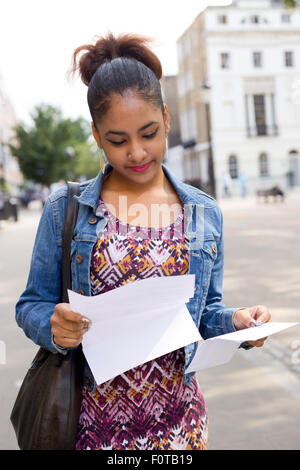 young woman reading a letter in the street - Stock Photo