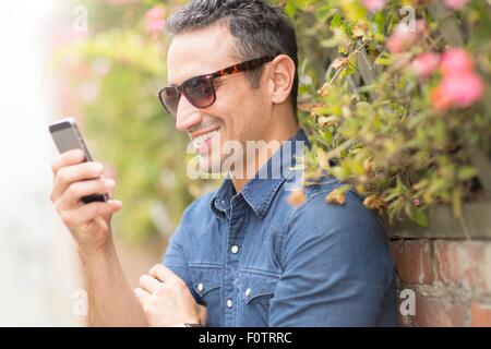 Mid adult man, outdoors, using mobile phone - Stock Photo