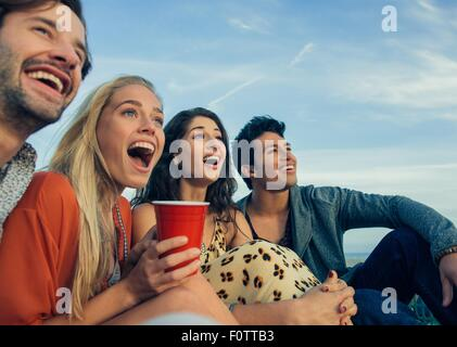 Group of friends sitting together outdoors, laughing - Stock Photo