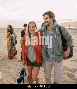 Group of friends walking along beach, young couple looking at smartphone - Stock Photo