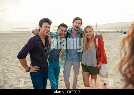 Group of friends standing together on beach, laughing - Stock Photo