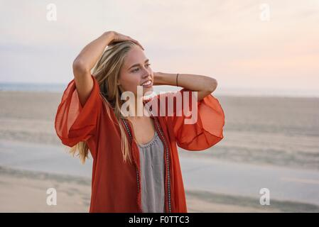 Young woman standing on beach, looking at view - Stock Photo
