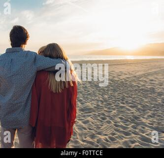 Young couple standing on beach, hugging, rear view - Stock Photo