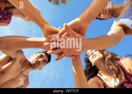 Group of friends joining hands on beach, low angle view - Stock Photo