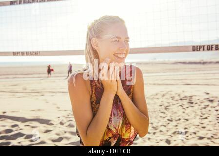 Young woman standing on beach by volleyball net, laughing - Stock Photo