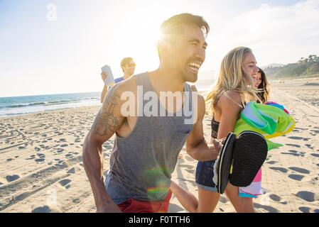 Group of friends walking on beach, laughing - Stock Photo