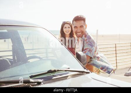 Young couple standing by car, at beach, laughing - Stock Photo
