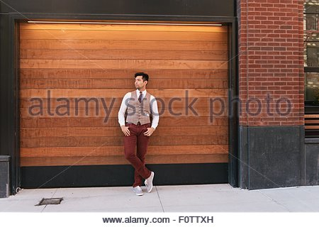 Stylish mid adult man leaning against shutter, West Village, Manhattan, USA - Stock Photo