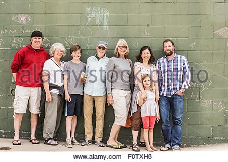 Three generation family in front of wall, portrait - Stock Photo