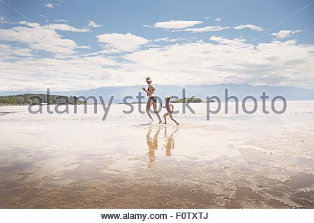 Mature woman running in sea with son, Lopar, Rab Island, Croatia - Stock Photo