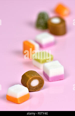 Trail of dolly mixtures on pink background - Stock Photo