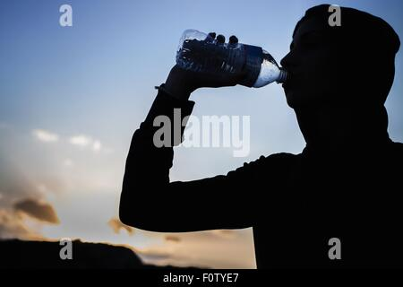 Young woman drinking from water bottle - Stock Photo