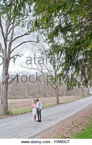 Portrait of bride and groom on country road - Stock Photo