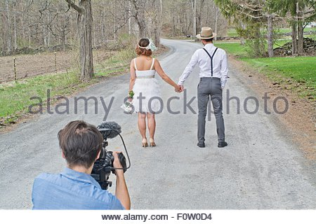Bride and groom on country road, holding hands, rear view, videographer in shot - Stock Photo