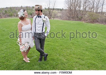 Portrait of bride and groom standing in field, face to face, smiling - Stock Photo