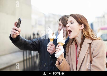 Couple with ice cream cones taking smartphone selfie, London, UK - Stock Photo