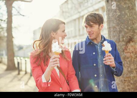 Couple eating ice cream cones whilst strolling along street, London, UK - Stock Photo
