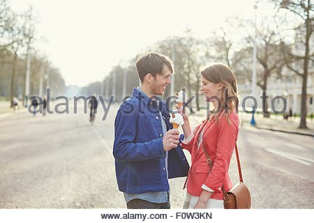 Couple eating ice cream cones in park, London, UK - Stock Photo