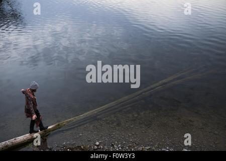 Woman balancing on fallen tree trunk in lake - Stock Photo