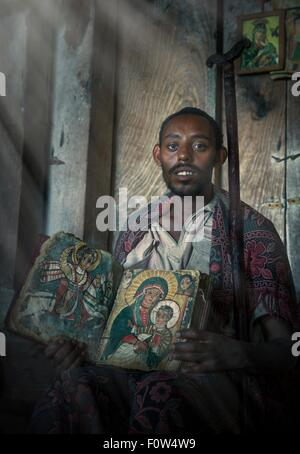 Portrait of priest with an old religious book in Ashen Maria Monastery, Lalibela, Ethiopia, Africa - Stock Photo