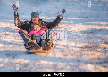 Portrait of smiling father and daughter riding sledge downhill in the snow - Stock Photo