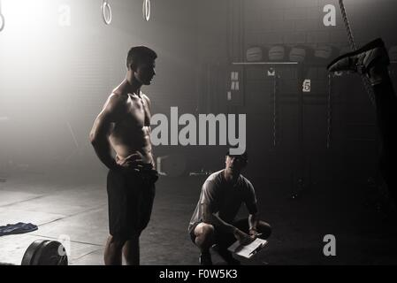 Young man and trainer in gym - Stock Photo