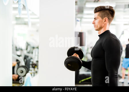 Young handsome man working out in a gym and lifting weights - Stock Photo