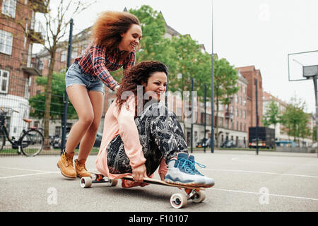 Happy young girl sitting on longboard being pushed by her friend. Young women enjoying skating outdoor. - Stock Photo