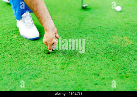 Golf player repairing divot on a green grass surface - Stock Photo