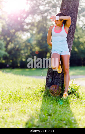 Young woman being exhausted after exercising in nature - Stock Photo