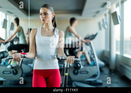 Beautiful, young woman lifting weights in a gym standing next to a mirror - Stock Photo