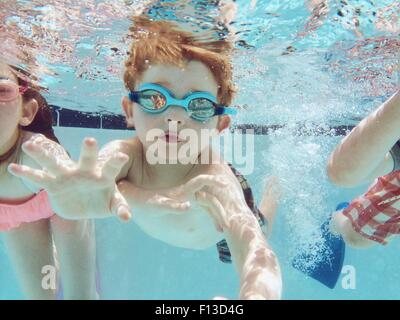 Portrait of a boy swimming underwater with friends - Stock Photo