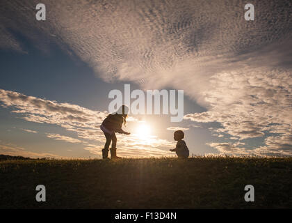 Silhouette of a girl with a baby learning to walk - Stock Photo