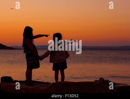 Silhouette of two girls at sunset, pointing - Stock Photo