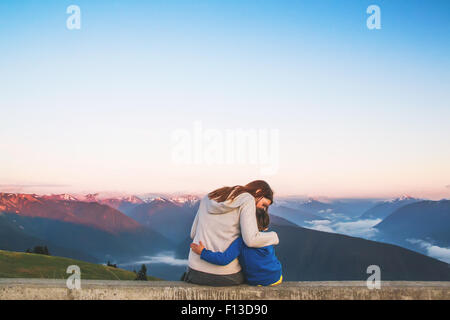 Rear view of woman sitting on a wall hugging her son - Stock Photo