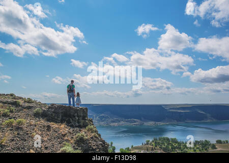 Rear view of father and daughter standing on top of a mountain - Stock Photo