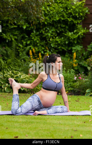 Pregnant woman doing yoga in the garden - Stock Photo