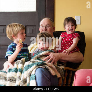 Three children sitting on their grandfather's lap - Stock Photo
