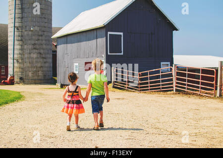 Rear view of a girl and boy holding hands, walking towards farm buildings - Stock Photo