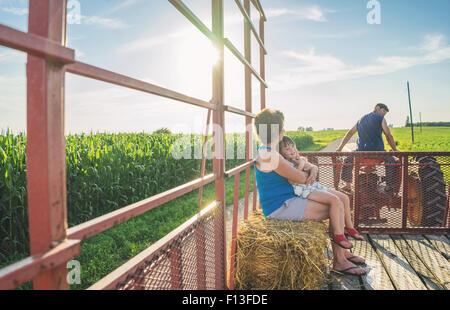 Mother sitting with her daughter in the back of a tractor - Stock Photo