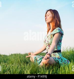 Pretty woman meditate in the park - Stock Photo