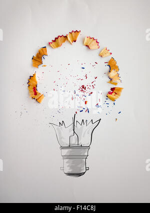 hand drawn light bulb with pencil saw dust on paper background as creative concept - Stock Photo