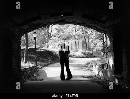 1960s SILHOUETTE OF ANONYMOUS YOUNG COUPLE EMBRACING KISSING AT ENTRANCE TO CENTRAL PARK TUNNEL NEW YORK CITY USA - Stock Photo